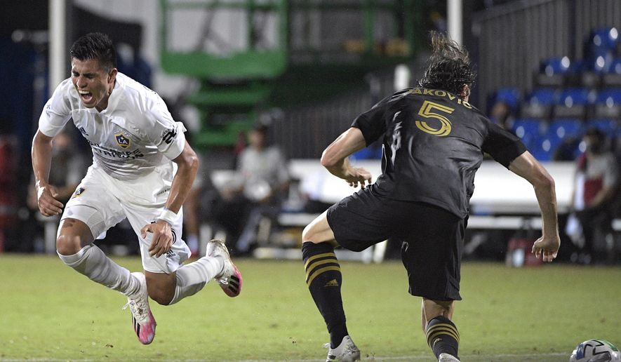 LA Galaxy midfielder Joe Corona (15) flies through the air after being separated from the ball by Los Angeles FC defender Dejan Jakovic (5) during the first half of an MLS soccer match, Saturday, July 18, 2020, in Kissimmee, Fla. (AP Photo/Phelan M. Ebenhack)