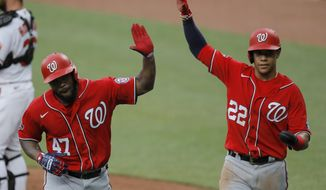 "Washington Nationals' Howie Kendrick (47) is greeted with ""air high fives"" by Juan Soto (22) after Kendrick scored them both on a two-run home run off Baltimore Orioles starting pitcher Alex Cobb during an exhibition baseball game, Monday, July 20, 2020, in Baltimore. (AP Photo/Julio Cortez)"