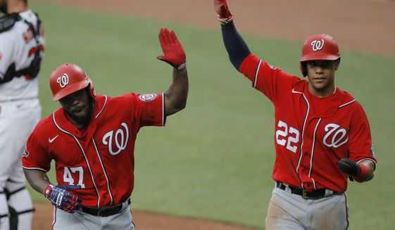 """Washington Nationals' Howie Kendrick (47) is greeted with """"air high fives"""" by Juan Soto (22) after Kendrick scored them both on a two-run home run off Baltimore Orioles starting pitcher Alex Cobb during an exhibition baseball game, Monday, July 20, 2020, in Baltimore. (AP Photo/Julio Cortez)"""