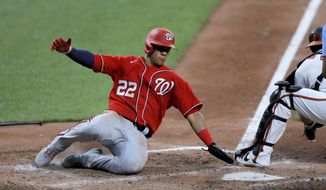 Washington Nationals' Juan Soto, left, slides in ahead of a tag by Baltimore Orioles catcher Austin Wynns while scoring on a double by Howie Kendrick during an exhibition baseball game Monday, July 20, 2020, in Baltimore. (AP Photo/Julio Cortez) ** FILE **