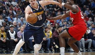 FILE - A Feb. 4, 2020, file photo, Denver Nuggets center Nikola Jokic, left, drives past Portland Trail Blazers forward Caleb Swanigan in the second half of an NBA basketball game in Denver. (AP Photo/David Zalubowski, File)