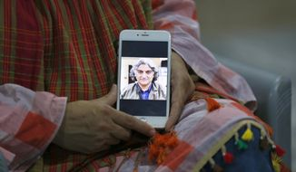 Kaneez Sughra, wife of kidnaped prominent Pakistani journalist Matiullah Jan, shows a picture her husband to journalists at a relative's home, in Islamabad, Pakistan, Tuesday, July 21, 2020. Jan, known for his hard hitting criticism of the country's powerful institutions, including its military, is missing, human rights groups and a family member said Tuesday. (AP Photo/Anjum Naveed)