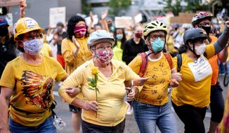 """FILE - In this July 20, 2020, file photo, Norma Lewis holds a flower while forming a """"wall of moms"""" during a Black Lives Matter protest in Portland, Ore. When armed protesters took over a remote wildlife refuge in eastern Oregon four years earlier to oppose federal control of public lands, U.S. agents negotiated with the conservative occupiers for weeks while some state leaders begged for stronger action. In July 2020, federal officers sent to Portland, Ore., to quell chaotic protests against racial injustice took swift and, some say, harsh action: launching tear gas, firing less-lethal ammunition and helping arrest more than 40 people in the first two weeks. (AP Photo/Noah Berger, File)"""