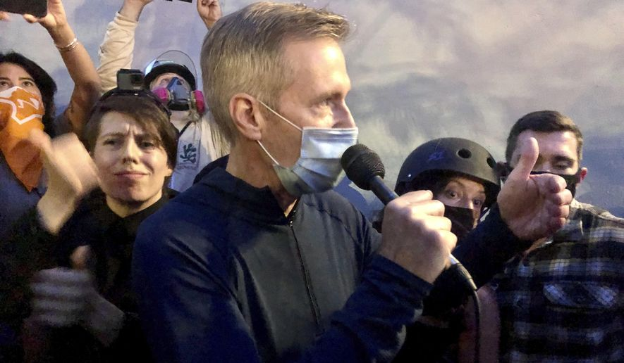 Mayor Ted Wheeler speaks to people gathered in downtown Portland, Ore., Wednesday, July 22, 2020. Wheeler faced a hostile crowd of protesters, who screamed at and sharply questioned him as he tried to rally demonstrators who have clashed repeatedly with federal agents sent in by President Donald Trump to quell ongoing unrest in the city. (AP Photo/Gillian Flaccus)