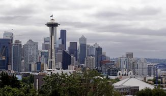 A flag with the new logo for the newly named Seattle NHL hockey team, the Seattle Kraken, flies atop the iconic Space Needle and in view of the team's arena, lower right, Thursday, July 23, 2020, in Seattle. (AP Photo/Elaine Thompson) ** FILE **