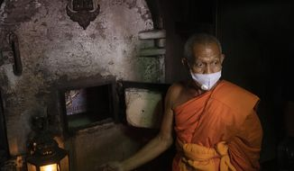A Buddhist monk talks to media after putting the coffin of the infamous Si Ouey into an incinerator for cremation at Wat Bang Phraek Tai temple Nonthaburi province, Thailand, Thursday, July 23, 2020. The corpse of Si Ouey, a notorious figure who was convicted of murder in 1959 and accused of cannibalism, was put on museum display for six decades, but an online campaign last year was successful in having him be given a proper funeral. (AP Photo/Sakchai Lalit)