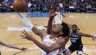 FILE - In this Feb. 27, 2020, file photo, Oklahoma City Thunder guard Shai Gilgeous-Alexander (2) shoots in front of Sacramento Kings forward Harry Giles III (20) during the first half of an NBA basketball game in Oklahoma City. The Thunder were one of the hottest teams in the NBA before the coronavirus pandemic hit. (AP Photo/Sue Ogrocki, File)