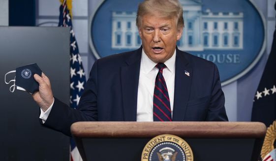 President Donald Trump holds a mask as he speaks during a news conference at the White House, Tuesday, July 21, 2020, in Washington. (AP Photo/Evan Vucci)