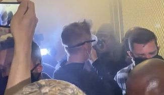 In this image made from video released by Jonathan Maus, Portland Mayor Ted Wheeler, center in black with goggles looking away, stands at a fence guarding a federal courthouse as tear gas drifts by early July 23, 2020, in Portland Oregon, during another night of protest against the presence of federal agents sent by President Donald Trump to quell unrest in the city. (Jonathan Maus/BikePortland via AP)