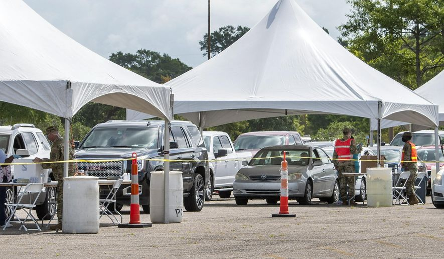 People line up at the Covid-19 testing site at Cortana Mall, Tuesday July 7, 2020, in Baton Rouge, La. (Bill Feig/The Advocate via AP)