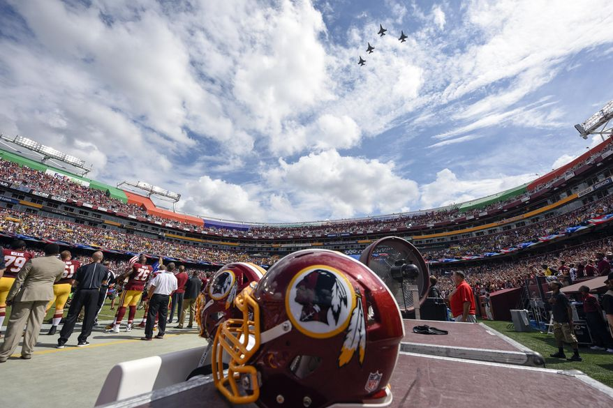 FILE - In this Sept. 18, 2016, file photo, F-26 fighter jets from the DC Air National Guard fly over FedEx Field before an NFL football game against between the Washington Redskins and the Dallas Cowboys in Landover, Md. A person with knowledge of the move tells The Associated Press the team formerly known as Redskins will go by Washington Football Team until a new name is chosen. Washington will keep its burgundy and gold colors and replace the Indian head logo on helmets with a player's jersey number.  (AP Photo/Nick Wass, File)