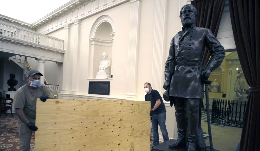 Workmen place plywood beside the statue of Robert E. Lee in the Old House Chamber inside the Virginia State Capitol in Richmond, Va., Thursday, July 23, 2020. All busts and plaques relating to the Confederacy were removed.  (Bob Brown/Richmond Times-Dispatch via AP)
