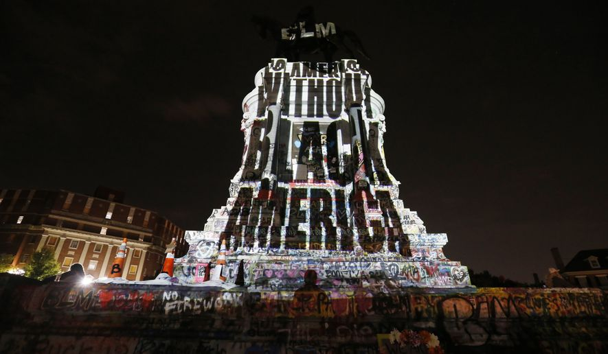 An image stating 'No America Without Black America' is projected on to the pedestal of the statue of Confederate Gen. Robert E. Lee on Monument Avenue Wednesday, July 22, 2020, in Richmond, Va. The statue has become a focal point for the Black Lives Matter protests in the area. (AP Photo/Steve Helber)