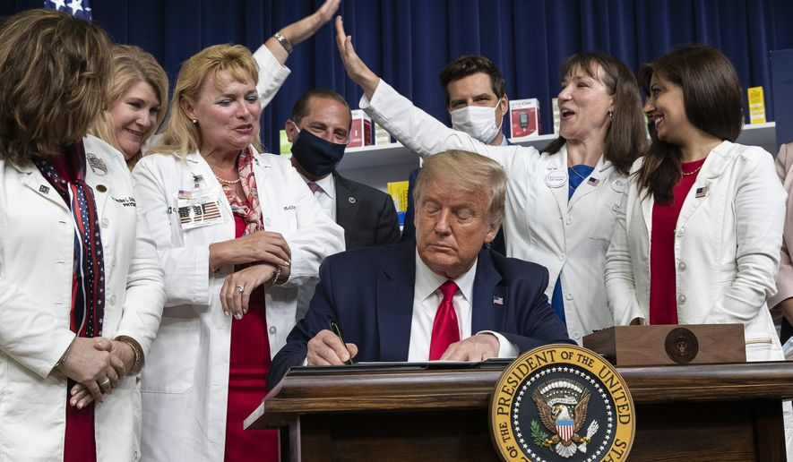 Supporters high five as President Donald Trump signs an executive orders on lowering drug prices, in the South Court Auditorium in the White House complex, Friday, July 24, 2020, in Washington. (AP Photo/Alex Brandon)