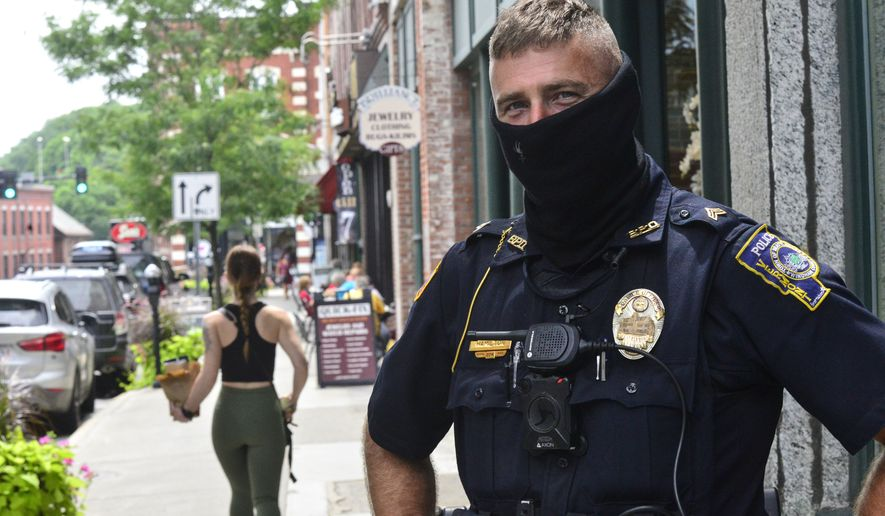 Brattleboro, Vt., Police Officer Jason Hamilton patrols around Brattleboro while wearing a mask on Friday, July 24, 2020. Vermont Gov. Phil Scott said in a press conference that starting Aug. 1, masks will be mandatory in public.  (Kristopher Radder/The Brattleboro Reformer via AP)