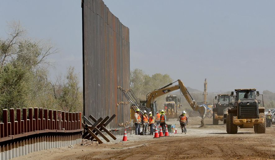 In this Sept. 10, 2019 file photo government contractors erect a section of Pentagon-funded border wall along the Colorado River in Yuma, Ariz. The federal Bureau of Land Management said on Tuesday, July 21, 2020, it's transferred over 65 acres of public land in Arizona and New Mexico to the Army for construction of border wall infrastructure. (AP Photo/Matt York, File)
