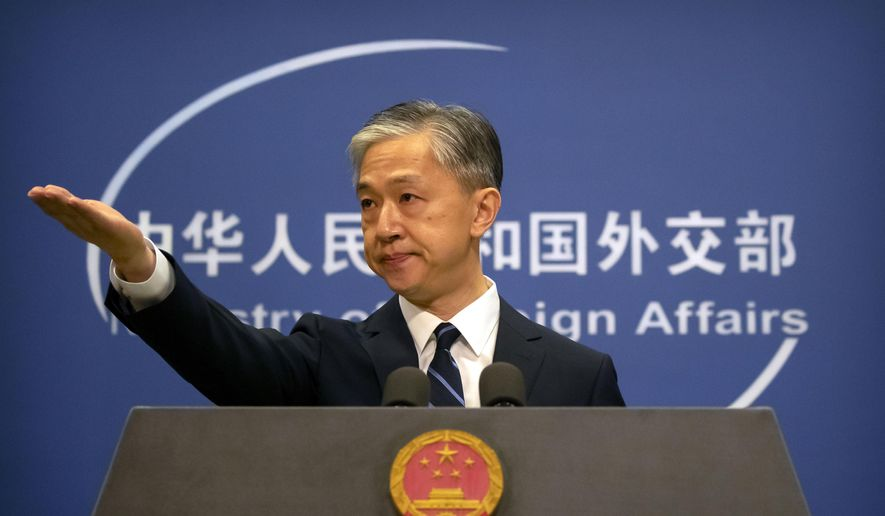 China's Ministry of Foreign Affairs spokesperson Wang Wenbin gestures during a daily briefing at the Ministry of Foreign Affairs in Beijing, Friday, July 24, 2020. (AP Photo/Mark Schiefelbein)