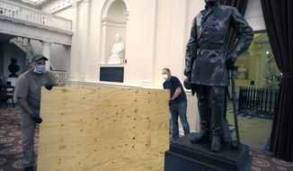 Workmen place plywood beside the statue of Robert E. Lee in the Old House Chamber inside the Virginia State Capitol in Richmond, VA Thursday night, July 23, 2020. All busts and plaques relating to the Confederacy were removed.  (Bob Brown/Richmond Times-Dispatch via AP)