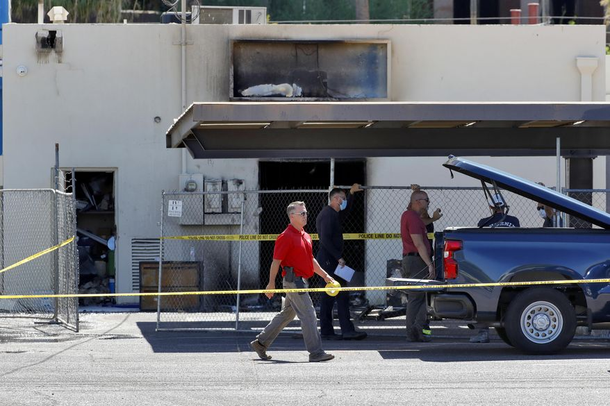 Fire investigators stand outside the Arizona Democratic Party headquarters Friday, July 24, 2020, in Phoenix. Fire investigators are looking into the cause of an early morning blaze that destroyed part of the Arizona and Maricopa County Democratic Party headquarters Friday. (AP Photo/Matt York)