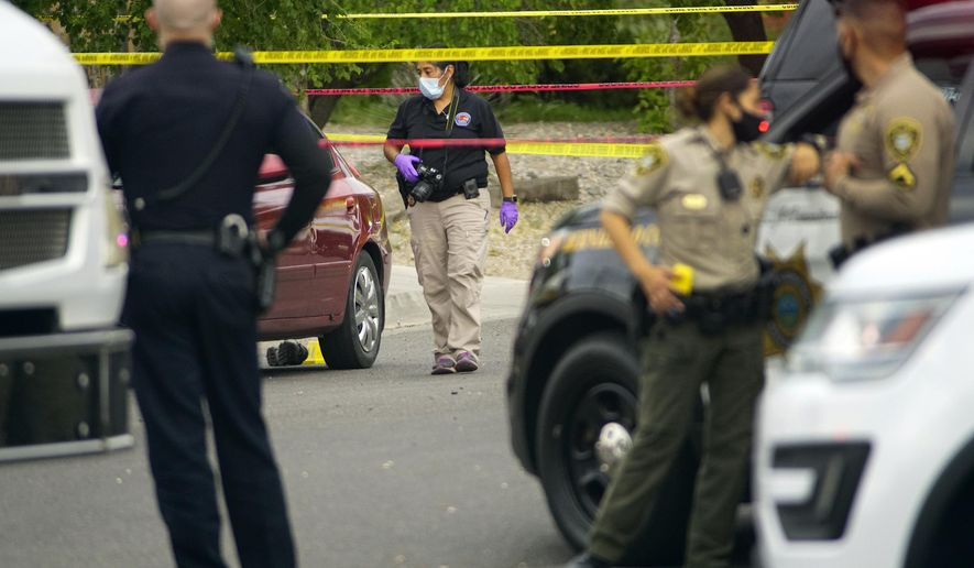 Albuquerque police and Bernalillo County deputies at the scene of a double shooting on the west side of Albuquerque, New Mexico, the result of a confrontation over a mask on Tuesday July 21, 2020. (Adolphe Pierre-Louis/The Albuquerque Journal via AP)