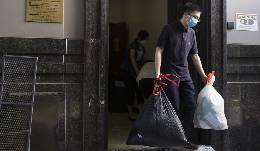 Consulate workers remove items from the Consulate General of China Friday, July 24, 2020, in Houston.  The U.S.government has ordered the Houston consulate to close by Friday. (Brett Coomer/Houston Chronicle via AP)