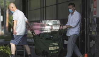 In this file photo, consulate workers carry diplomatic bags from the Consulate General of China Friday, July 24, 2020, in Houston.  The U.S.government has ordered the Houston consulate to close by Friday. (Brett Coomer/Houston Chronicle via AP)   **FILE**