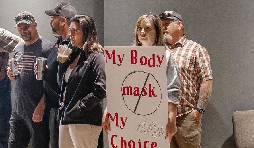 A woman holds a sign in protest of a potential mask requirement during a Gallatin Board of Health meeting on Tuesday, July 14, 2020 in Bozeman, Mont. Montana's Gallatin County became the latest battleground over mandating masks to slow the coronavirus on Friday, July 24, as dozens pushed back against new rules in a virtual face-off with public health officials. (Zach Meyer/Bozeman Daily Chronicle via AP)/