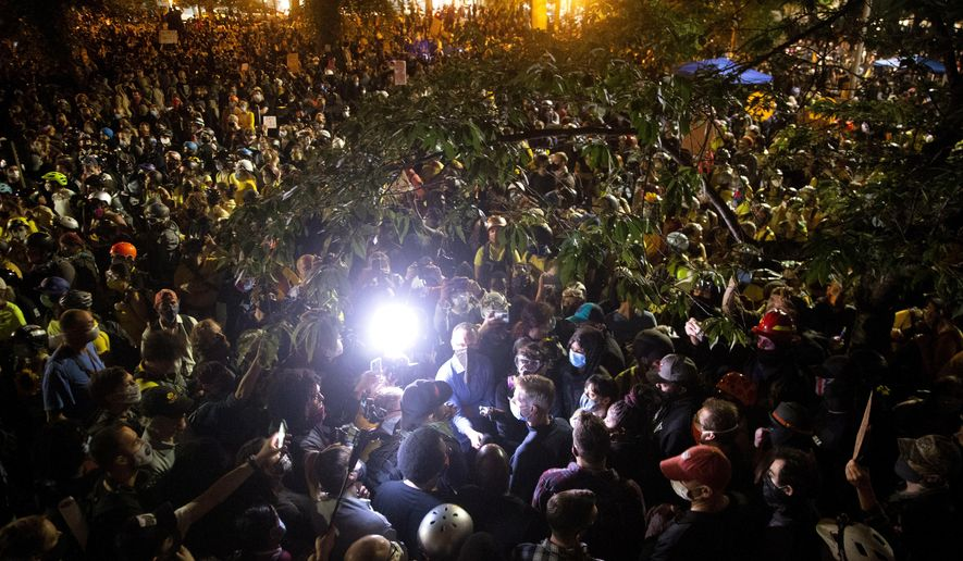"Portland Mayor Ted Wheeler wades through the large crowd, where his stated goal was to conduct a ""listening session,"" during a night of protest in Portland,Wednesday,  July 22, 2020. (Beth Nakamura/The Oregonian via AP)"