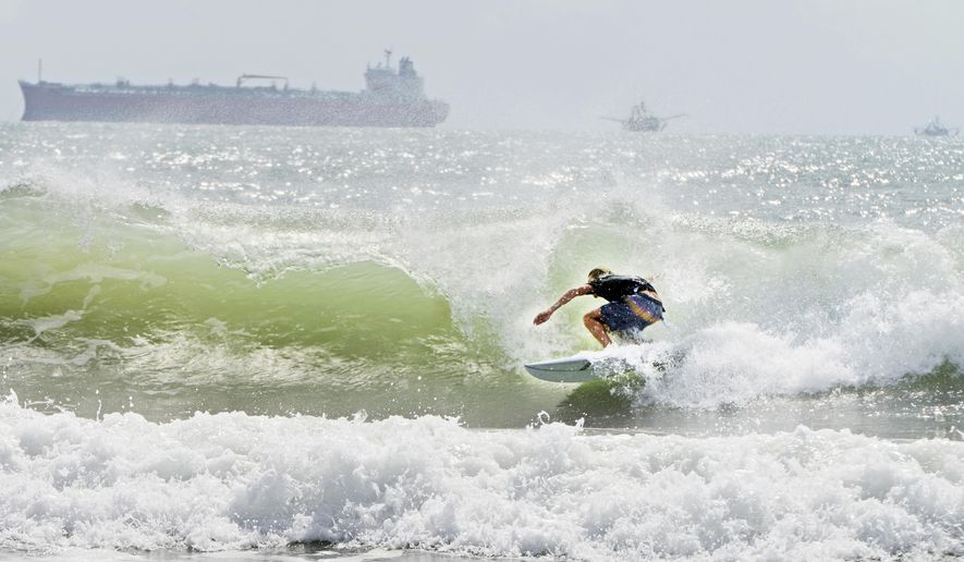 A surfer catches a barrel ride Friday, July 24, 2020, as swell waves approach the coast of South Padre Island, Texas, due to Tropical Storm Hanna approaching the Texas Gulf Coast. (Miguel Roberts/The Brownsville Herald via AP)