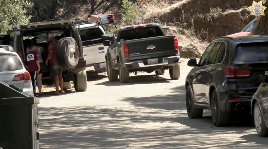 In this Wednesday, July 22, 2020, photo taken from a video public service announcement by the Placer County Sheriff's Office, Yankee Jims Road is choked with traffic by people seeking to visit the former Sierra Nevada Gold Rush mining area near the town of Yankee Jims, Calif. California State Parks banned public parking on narrow Yankee Jims Road in the middle of Placer County gold country within Auburn State Recreation Area to reduce the risk of COVID-19 exposures after social-media-fueled surges in the number of visitors. Last weekend, there were more than 300 vehicles parked in an area with legal room for only 12. (Angela Musallam/Placer County Sheriff's Office via AP)