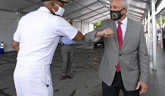 Vice Admiral Jerome Adams, the U.S. Surgeon General, greets Miami-Dade County Mayor Carlos Gimenez with an elbow bump at the COVID-19 drive-thru testing center at Miami-Dade County Auditorium in Miami as the novel coronavirus pandemic continues on Thursday, July 23, 2020.(David Santiago/Miami Herald via AP)