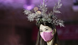 A model wearing a face mask poses during a mask fashion show amid the coronavirus pandemic in Seoul, South Korea, Friday, July 24, 2020. (AP Photo/Lee Jin-man)