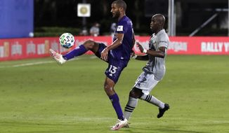 Orlando City forward Tesho Akindele (13) works the ball against Montreal Impact defender Rod Fanni (7) during the first half of an MLS soccer match, Saturday, July 25, 2020, in Kissimmee, Fla. (AP Photo/John Raoux)