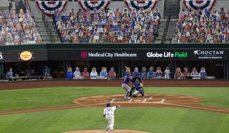 Texas Rangers starter Lance Lynn (35) throws the first pitch of an opening day baseball game to Colorado Rockies' David Dahl as Rangers' Robinson Chirinos catches and home plate umpire Jim Reynolds looks on Friday, July 24, 2020, in Arlington, Texas. The pitch was the first ever in a regular season game at Globe Life Field, the Rangers' new ballpark. (AP Photo/Jeffrey McWhorter)