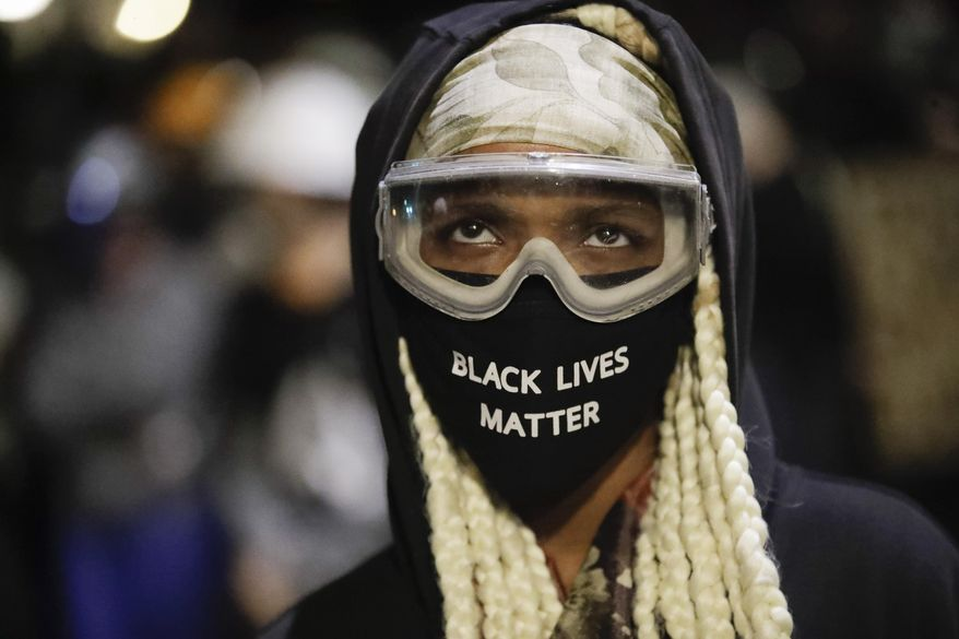 A protester wears a mask and googles outside the Mark O. Hatfield United States Courthouse during a Black Lives Matter protest Friday, July 24, 2020, in Portland, Ore. (AP Photo/Marcio Jose Sanchez)