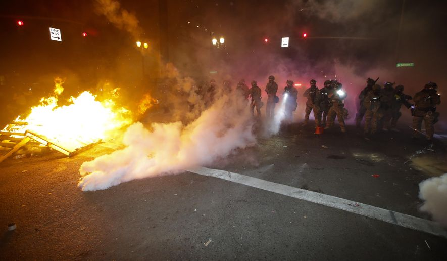 Federal officers clear a street where demonstrator had set a fire during a Black Lives Matter protest at the Mark O. Hatfield United States Courthouse Saturday, July 25, 2020, in Portland, Ore. (AP Photo/Marcio Jose Sanchez)