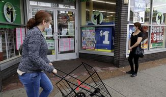 FILE - In this Friday, May 15, 2020, file photo, a woman wearing a mask, left, walks by a Dollar Tree, while another woman waits in line to shop at the store, which is limiting customers amid the coronavirus pandemic, in Chicago. (AP Photo/Nam Y. Huh, File)