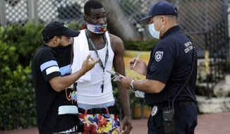 A man covers his nose with his shirt, left, as Luis Negron, a Miami Beach code compliance officer, right, talks to him about wearing a protective face mask amid the coronavirus pandemic, Friday, July 24, 2020, on Ocean Drive in Miami Beach, Fla. Masks are mandated both indoors and outdoors in Miami Beach. People found not wearing a mask are subject to a civil fine of $50. (AP Photo/Lynne Sladky)