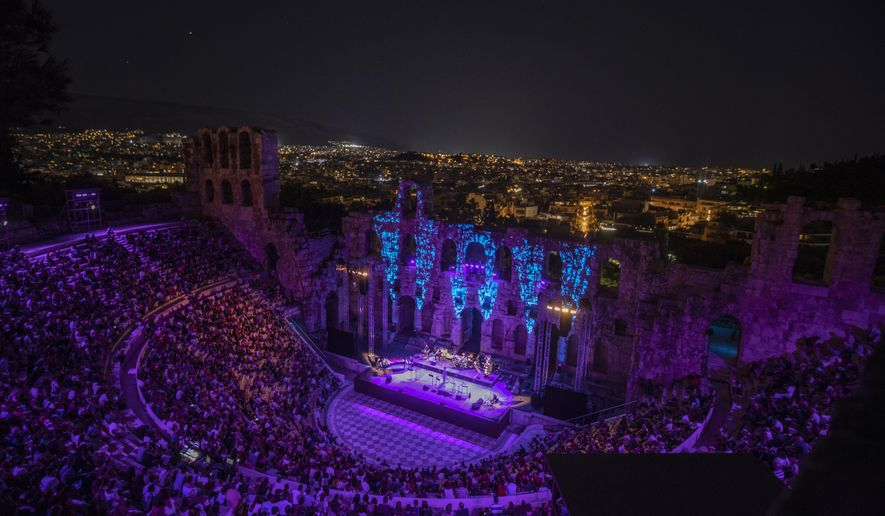 Spectators listen a concert at Odeon of Herodes Atticus as the city of Athens is seen on the background on Wednesday, July 15, 2020. The ancient theaters of Herodes Atticus in Athens and Epidaurus in the southern Peloponnese area have reopened for performances with strict seating limits and public health safety guidelines. (AP Photo/Petros Giannakouris)