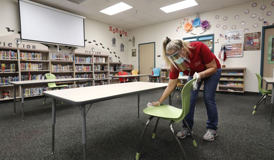Wearing a mask and face guard as protection against the spread of COVID-19, Garland Independent School District custodian Maria Concha wipes down a chair in the library at Stephens Elementary School in Rowlett, Texas, Wednesday, July 22, 2020.(AP Photo/LM Otero)
