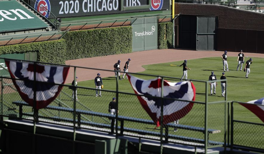 Milwaukee Brewers players warm up before an opening day baseball game against the Chicago Cubs in Chicago, Friday, July 24, 2020, in Chicago. In a normal year, that would mean a sellout crowd at Wrigley Field and jammed bars surrounding the famed ballpark but in a pandemic-shortened season, it figures to be a different atmosphere. (AP Photo/Nam Y. Huh)