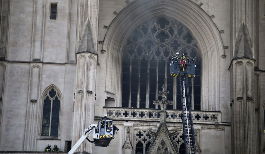 Fire fighters brigade work to extinguish the blaze at the Gothic St. Peter and St. Paul Cathedral, in Nantes, western France, July 18, 2020. French authorities detained and charged a repentant church volunteer Sunday, July 26, 2020 after he told investigators that he was responsible for an arson attack that badly damaged a 15th-century Gothic cathedral. (AP Photo/Romain Boulanger) ** FILE **