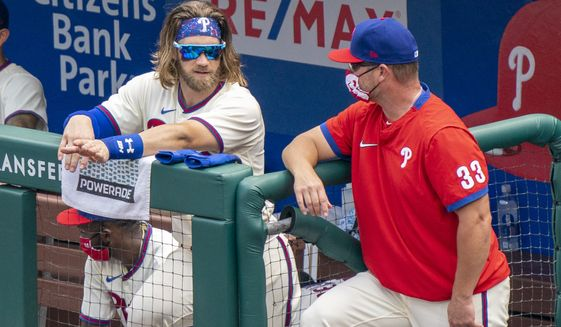 Philadelphia Phillies' Bryce Harper, left, talks things over with hitting coach Joe Dillon, right, during the first inning of a baseball game against the Miami Marlins, Sunday, July 26, 2020, in Philadelphia. The Marlins won 11-6. (AP Photo/Chris Szagola) ** FILE **
