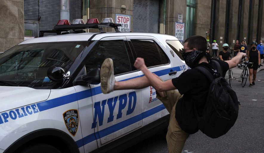 """A protester kicks a police vehicle in an attempt to break its side mirror during a """"Solidarity with Portland"""" protest Saturday, July 25, 2020, in New York. (AP Photo/Yuki Iwamura)"""
