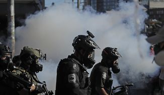Seattle police officers wear gas masks and carry weapons as smoke rises and they clash with protesters, Saturday, July 25, 2020, in Seattle during a protest in support of Black Lives Matter and against police brutality and racial injustice. (AP Photo/Ted S. Warren)
