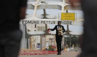 A man places flower petals on the Edmund Pettus Bridge ahead of Rep. John Lewis' casket crossing during a memorial service for Lewis, Sunday, July 26, 2020, in Selma, Ala. Lewis, who carried the struggle against racial discrimination from Southern battlegrounds of the 1960s to the halls of Congress, died Friday, July 17, 2020. (AP Photo/Brynn Anderson)