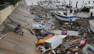 Allen Heath surveys the damage to a private marina after it was hit by Hurricane Hanna, Sunday, July 26, 2020, in Corpus Christi, Texas. Heath's boat and about 30 others were lost or damaged. (AP Photo/Eric Gay)