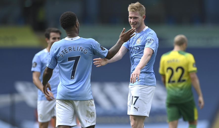 Manchester City's Kevin De Bruyne, right, celebrates after scoring his side's second goal with Manchester City's Raheem Sterling during the English Premier League soccer match between Manchester City and Norwich City at the Etihad Stadium in Manchester, England, Sunday, July 26, 2020. (Shaun Botterill/Pool via AP)
