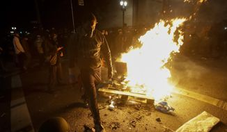 A protester walks past a bonfire set at an intersection during a Black Lives Matter protest at the Mark O. Hatfield United States Courthouse Saturday, July 25, 2020, in Portland, Ore. (AP Photo/Marcio Jose Sanchez)