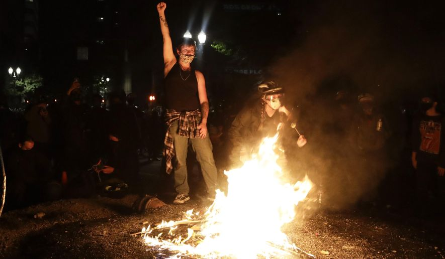 Demonstrators rally around a fire during a Black Lives Matter protest at the Mark O. Hatfield United States Courthouse Saturday, July 25, 2020, in Portland, Ore. (AP Photo/Marcio Jose Sanchez) **FILE**